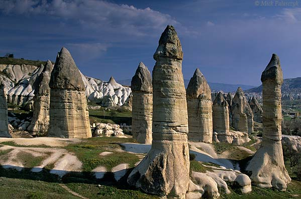 [TURKEY.CENTRAL 26799 'Fairy chimneys in Görkün Valley-5.'  	The Görkün Valley south of the Cappadocian village of Göreme boasts some of the most spectacular fairy chimneys. The pillars consist of tuff (consolidated volcanic ash) that has been protected from rain erosion by a cap of harder more solidified ash (ignimbrite). Photo Mick Palarczyk.