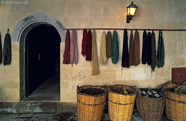 [TURKEY.CENTRAL 26782] 'Yarns and natural pigments.'  	Yarns hanging on display in the former caravanserai of Mustafapasa have been coloured with pigments extracted from flowers, leafs and bark that fill the baskets standing beneath them. The wool yarns are locally used for weaving carpets. Photo Mick Palarczyk.