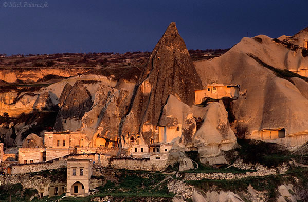 [TURKEY.CENTRAL 26788 'Cave-dwellings in Göreme.'  At the southern edge of the Cappadocian village of Göreme the warm light of the evening sun is lighting up dwellings that have been excavated in a thick layer of volcanic tuff. Photo Mick Palarczyk.