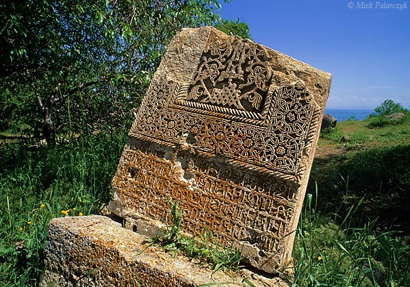 """[TURKEY.EAST 27943] 'Khatchkar on Akdamar Island-2.'  The lower part of beautifully carved khatchkar is standing north of the 10th century Armenian Cathedral of the Holy Cross on Akdamar, a small island in Lake Van. The carving of khatchkars (literally meaning """"cross stone"""") was an artistic Armenian tradition. The slabs were used for commemorative as well as funerary purposes. The khatchkars at Akdamar can be dated from the 13th to the 17th century. Photo Mick Palarczyk."""