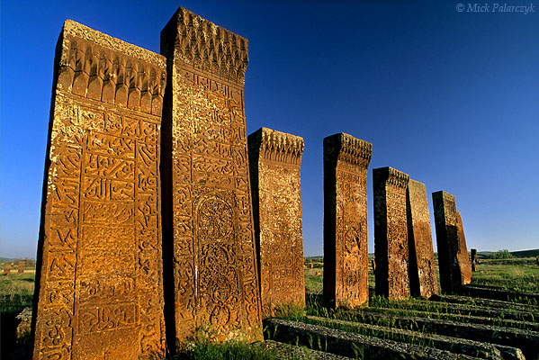 [TURKEY.EAST 27916] 'Ahlat cemetery in morning sun-2.'  	At the Seljuk cemetery of Ahlat, on the western shore of Lake Van, headstones of red volcanic tuff glow in the morning sun. The ca. 8000 steles, which can reach a height of 4 meter, date from the 12th and 13th century and are covered with intricate web patterns and Kufic lettering. Photo Mick Palarczyk.