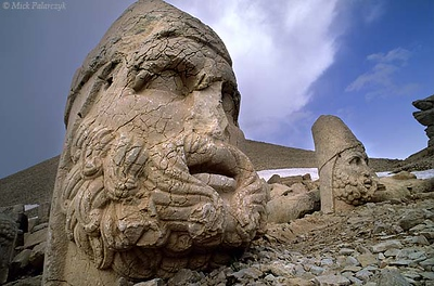 [TURKEY.EAST 27858] 'Hercules and Zeus on Nemrud Dag-2.'  On top of Mount Nemrud, east of Adiyaman, king Antiochus I (ca. 62 -32 BC) of Commagene built for himself a huge tumulus flanked by rows of giant statues. Commagene was a small independent kingdom squeezed between the Roman Empire and the Parthian (Persian) kingdom. The statues are syncretic deities that represent a fusion of ancient (Zoroastrian) Persian and Greek/Roman gods. Here we see, in the foreground Hercules/Artagnes and to the right Zeus/Ahuramazda. The heads have toppled from statues that occupy a terrace on the west side of the tumulus, which can be seen looming behind. Photo Mick Palarczyk.
