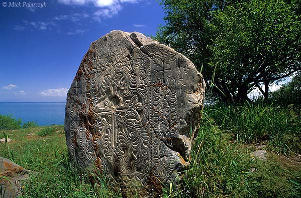 """[TURKEY.EAST 27942] 'Khatchkar on Akdamar Island-1.'  A beautifully carved khatchkar is standing north of the 10th century Armenian Cathedral of the Holy Cross on Akdamar, a small island in Lake Van. The carving of khatchkars (literally meaning """"cross stone"""") was an artistic Armenian tradition. The slabs were used for commemorative as well as funerary purposes. The khatchkars at Akdamar can be dated from the 13th to the 17th century. Photo Mick Palarczyk."""
