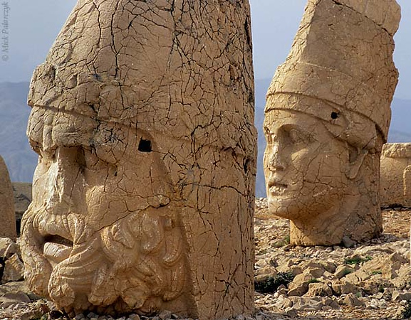 [TURKEY.EAST 27861] 'Hercules and Antiochus on Nemrud Dag-2.'  On top of Mount Nemrud, east of Adiyaman, king Antiochus I (ca. 62 -32 BC) of Commagene built for himself a huge tumulus flanked by rows of giant statues. Commagene was a small independent kingdom squeezed between the Roman Empire and the Parthian (Persian) kingdom. The statues are syncretic deities that represent a fusion of ancient (Zoroastrian) Persian and Greek/Roman gods. Here we see in the foreground Hercules/Artagnes and to the right Antiochus who placed himself among the gods. The heads have toppled from statues that occupy a terrace on the west side of the tumulus. Photo Mick Palarczyk.