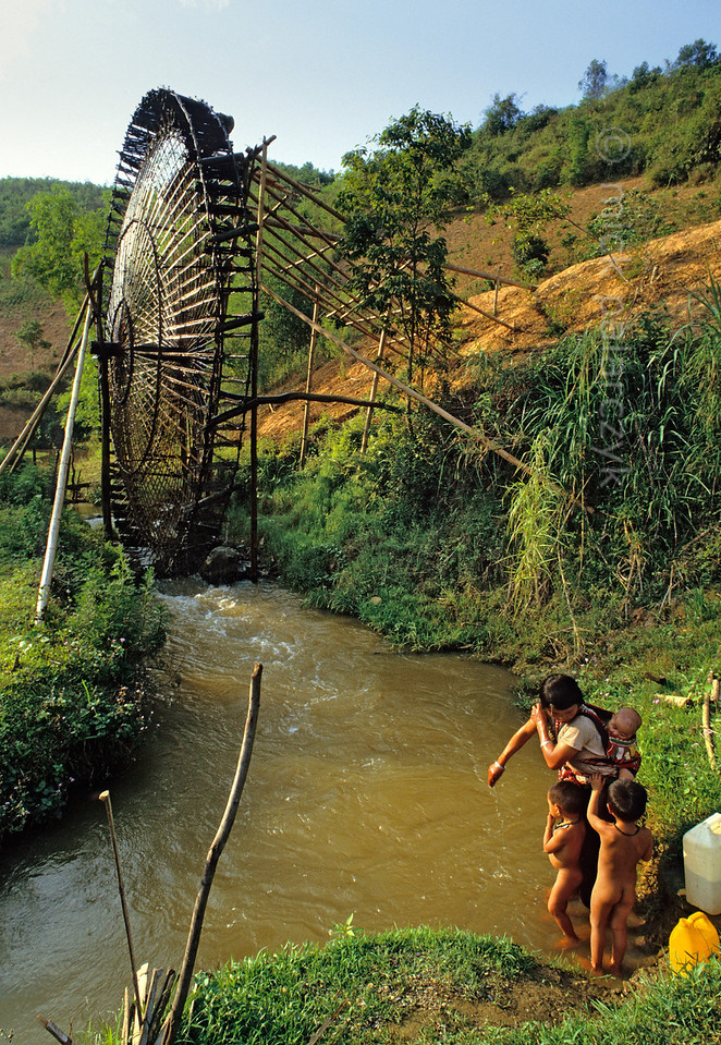 [VIETNAM.NORTH 21.282] 'Morning toilet near an irrigation wheel.'  	Near a bamboo made irrigation wheel, driven by the power of a tributary of the Nam La River, south of So'n La, a woman of the Black Thái mountain tribe is washing herself and her children. Photo Mick Palarczyk.