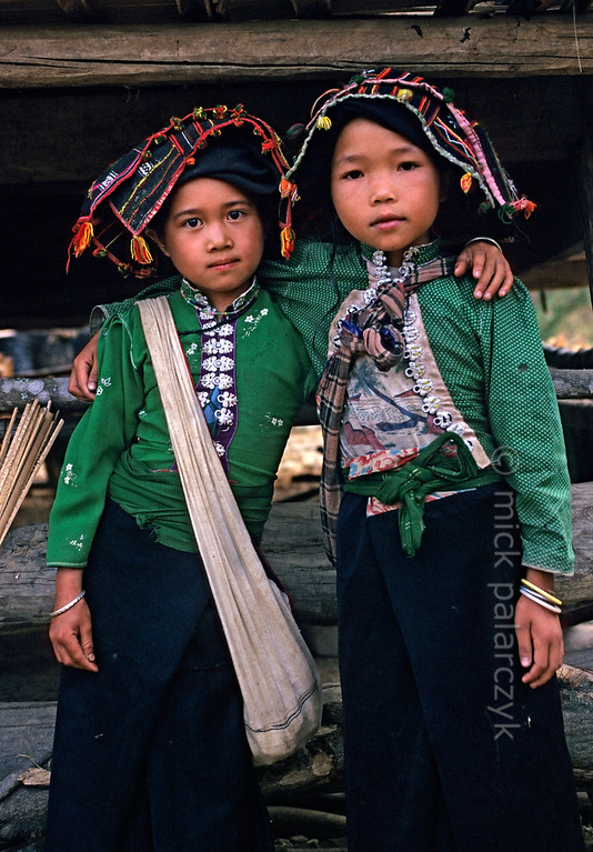 [VIETNAM.NORTH 21.342] 'Black Thái girls.'  	These girls in a village on the Pha Din Pass, 40 km northwest of So'n La, wear the traditional dress of the Black Thái: a brightly coloured blouse with a distinctive row of silver buttons down the front and a long black skirt. Photo Mick Palarczyk.
