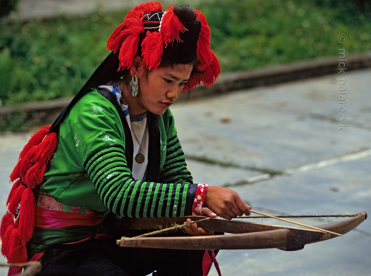 [VIETNAM.NORTH 21.351] 'White H'mông girl with cross-bow.'  In Tuân Giáo a White H'mông girl practises with a crossbow. Her traditional hat consists of a black headscarf with red tassels. Photo Mick Palarczyk.