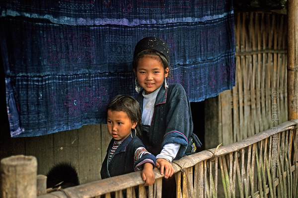 [VIETNAM.NORTH 21.452] 'Black H'mong girls in Lao Chai.'  	Two girls of the Black H'mong mountain tribe stand on the verandah of their house in Lao Chai village, 5 km east of Sapa. Behind them hangs a piece of indigo coloured cloth, decorated with the batik technique. In most H'mong villages basins with indigo dye can be found. Photo Mick Palarczyk