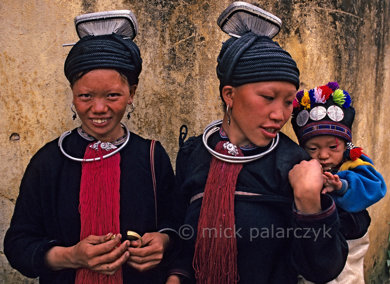 [VIETNAM.NORTH 21.403] 'Black Dao women with hair frame.'  The hair of these Black Dao women in Tam Duòng is kept in place by a large silver frame and a thick black cord which is wrapped around the head. The coins on the cap of the child must protect it against evil spirits. Photo Mick Palarczyk.