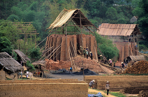 [VIETNAM.NORTH 21.259] 'Brick factory.'  	Workers laden with unfired bricks climb rickety stairs to fill the bowels of this brick factory in the valley of the Dà River at Ky Son near Hòa Binh. Photo Mick Palarczyk.