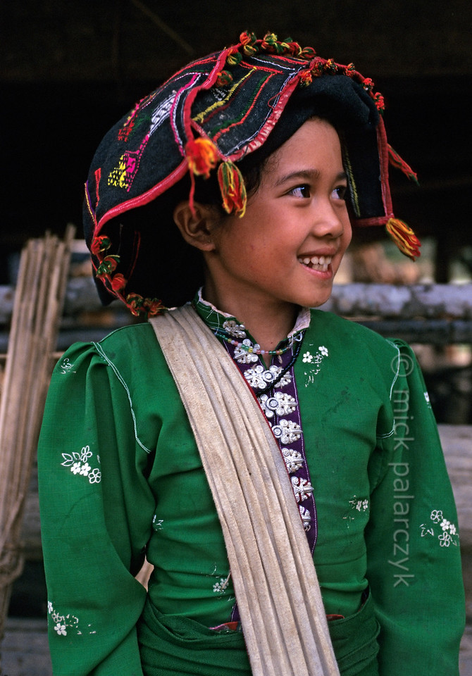 [VIETNAM.NORTH 21.344] 'Black Thái girl on Pha Din Pass.  This girl in a village on the Pha Din Pass, 40 km northwest of So'n La, wears the traditional dress of the Black Thái: a brightly coloured blouse with a distinctive row of silver buttons down the front and a long black skirt. Photo Mick Palarczyk.