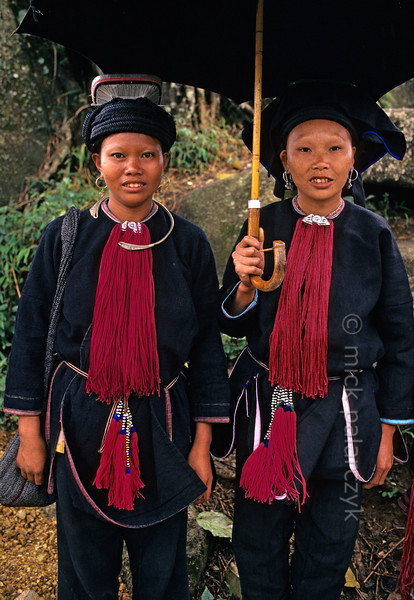 [VIETNAM.NORTH 21.388] 'Black Dao women under umbrella.'  	Black Dao women wear plain black trousers and jackets finished with a superb red ruff. The hair on their forehead is plucked (including the eyebrows) so that it cannot distract from the beauty of their clothing. Photo Mick Palarczyk.