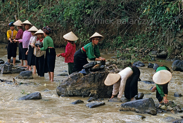 [VIETNAM.NORTH 21.301] 'Handing down boulders.'  	Black Thái tribes women hand down river boulders which are used to build a dam for an irrigation wheel in a tributary of the Nam La River, south of So'n La.. (See image 21.293). Photo Mick Palarczyk.