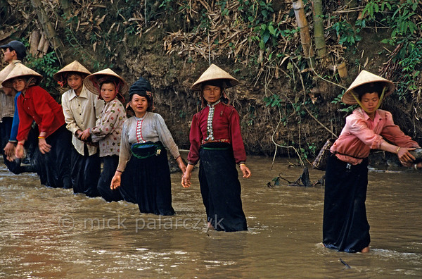 [VIETNAM.NORTH 21.302] 'Handing down boulders.'  	Black Thái tribes women hand down river boulders which are used to build a dam for an irrigation wheel in a tributary of the Nam La River, south of So'n La.. (See image 21.293). Photo Mick Palarczyk.