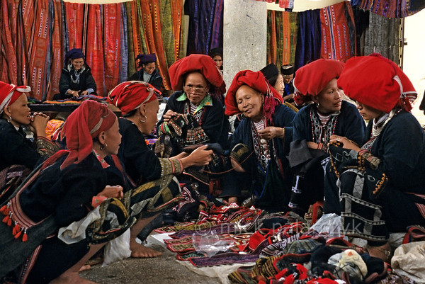 [VIETNAM.NORTH 21.423] 'Red Dao in sewing atelier.'  	In the sewing atelier on the market of Sapa Red Dao women are selling clothes and jewellery, working on embroidery and comparing decoration patterns . Photo Mick Palarczyk
