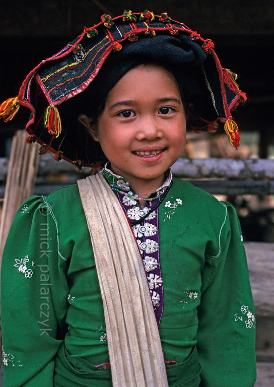 [VIETNAM.NORTH 21.346] 'Black Thái girl on Pha Din Pass.  This girl in a village on the Pha Din Pass, 40 km northwest of So'n La, wears the traditional dress of the Black Thái: a brightly coloured blouse with a distinctive row of silver buttons down the front and a long black skirt. Photo Mick Palarczyk.