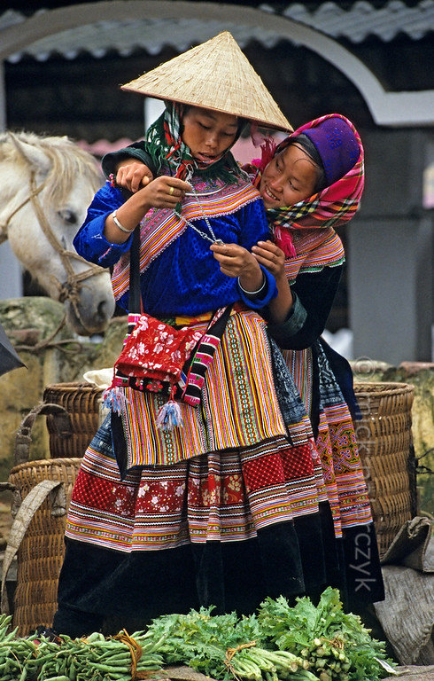 [VIETNAM.NORTH 21.504] 'Psychedelic embrace.'  Teenage Flower H'mong girls in a friendly embrace on the market of Bac Hà, discussing the beauty of a necklace. They wear a psychedelic combination of colours. Photo Mick Palarczyk