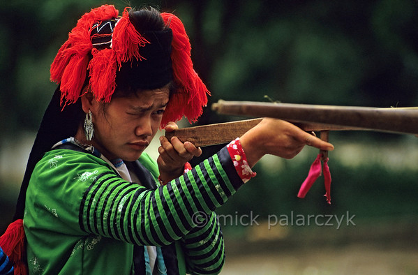 [VIETNAM.NORTH 21.349] 'White H'mông girl with cross-bow.'  	In Tuân Giáo a White H'mông girl practises with a crossbow. Her traditional hat consists of a black headscarf with red tassels. Photo Mick Palarczyk.