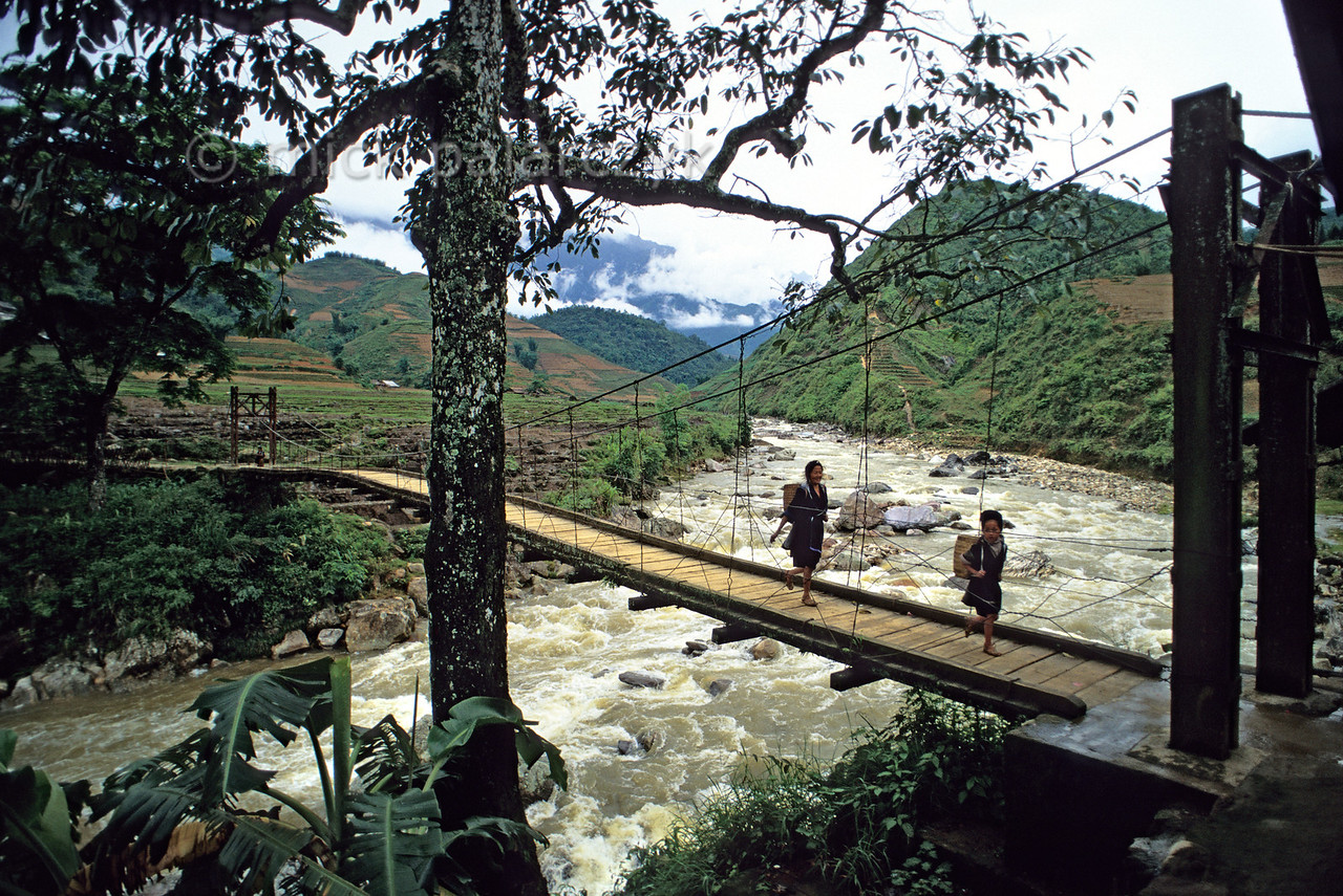 [VIETNAM.NORTH 21.475] 'Cloudy Bridge.'  East of Sapa a woman and a girl from the Black H'mong mountain tribe pass the so-called 'Cloudy Bridge' across the Muong Hoa River. Photo Mick Palarczyk