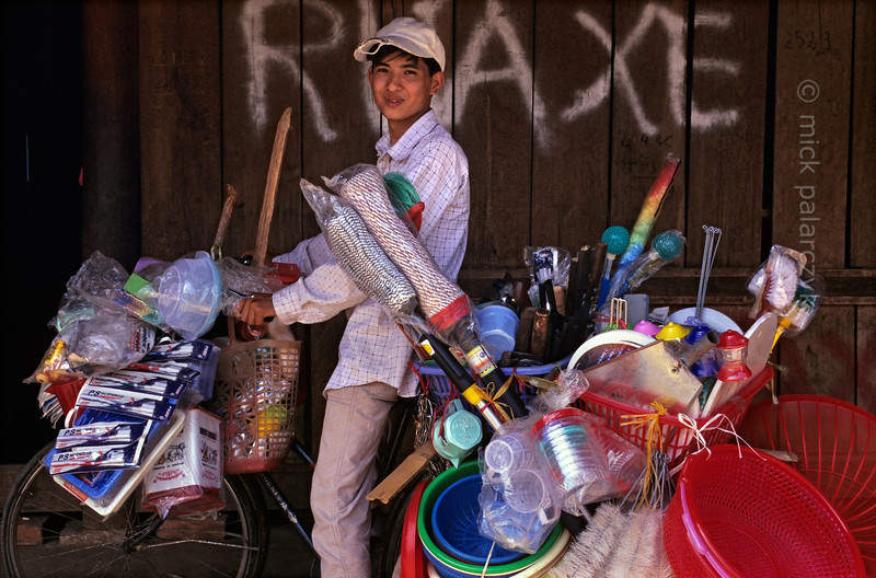 [VIETNAM.NORTH 21.338] 'Selling plastic.'  In mountain tribe villages that still mostly use self-made crockery and wooden tools this pedlar is an herald of modern times. Photo Mick Palarczyk.