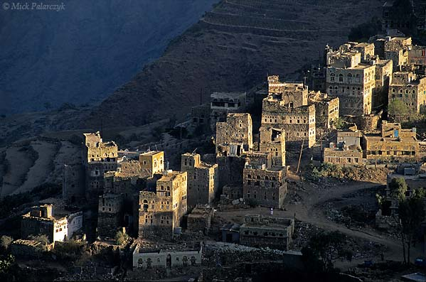 [YEMEN.NORTH 26283] 'Manakha tower houses-3.'  The tower houses of Manakha, a small town in the Jebel Haras mountains, catch the first rays of the sun. Photo Mick Palarczyk.