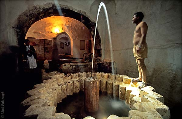 [YEMEN.NORTH 26373] 'Public bath.'  In the hamam (public bath) of Wadi Dahr village, northwest of Sanaa, a bather is about to take a dip in the star shaped cold bath. Photo Mick Palarczyk.