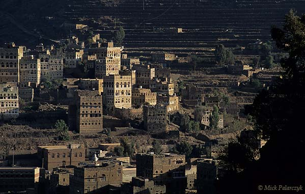 [YEMEN.NORTH 26278] 'Manakha tower houses-1.'  The tower houses of Manakha, a small town in the Jebel Haras mountains, catch the first rays of the sun. Photo Mick Palarczyk.