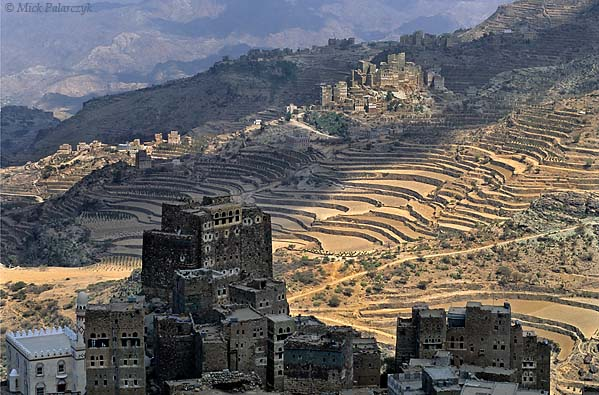 [YEMEN.NORTH 26335] 'Ben Ismael and Sherege.'  South of Manakha the tower houses of Ben Ismael village overlook the terraced slopes of the Jebel Haras mountains. In the background the village of Sherege catches a patch of sunlight. Photo Mick Palarczyk.