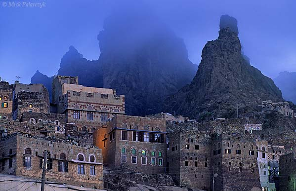 [YEMEN.NORTH 26275] 'Peaks in the fog.'  Evening fog closes in on the craggy peaks which tower above Manakha, a small town in the Jebel Haras mountains southwest of Manakha. Photo Mick Palarczyk.