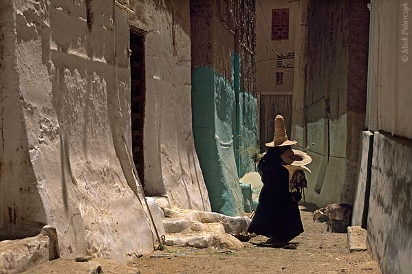 [YEMEN.SOUTH 26565] 'Witches' hats.'  	Returning from a morning's work in the field, women wearing tall straw witches' hats - known as madhalla - stroll through the alleys of Shibam, an ancient town in the Wadi Hadhramawt. Photo Mick Palarczyk.