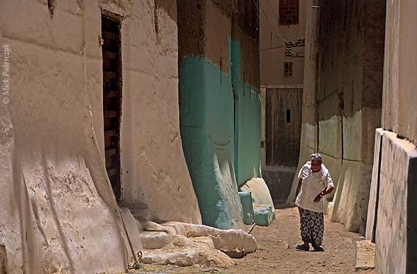 [YEMEN.SOUTH 26567] 'Alley in Shibam-1.'  	An alley in the southwestern part of Shibam, an ancient town in the Wadi Hadhramawt. The width of these alleys is determined by the space that is necessary for the passage of a fully laden camel with wobbling gait. Photo Mick Palarczyk.