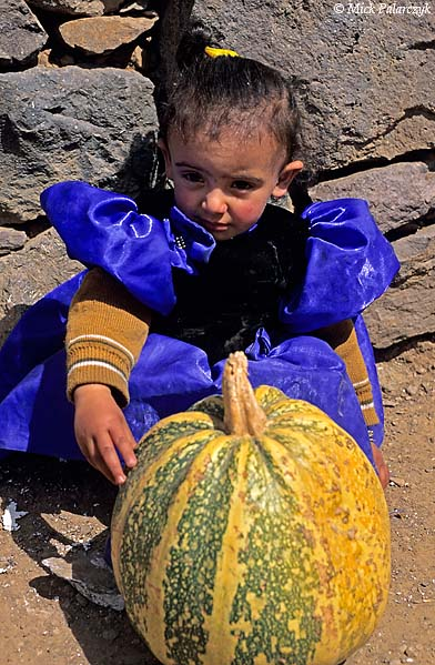 [YEMEN.NORTH 26307] 'Girl in Al Jebel.'  A young girl in Al Jebel village (in the Jebel Haras mountains) is allowed to play in her bright blue dress. When she gets older she will have to wear the black chador when she goes outside. Photo Mick Palarczyk.