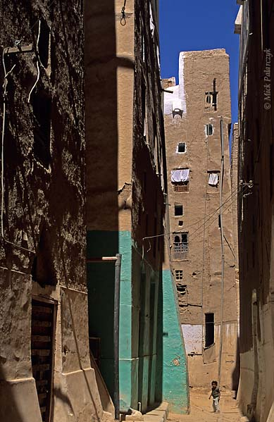 [YEMEN.SOUTH 26572] 'Alley in Shibam-2.'  	An alley in the western part of Shibam, an ancient town in the Wadi Hadhramawt. The width of these alleys is determined by the space that is necessary for the passage of a fully laden camel with wobbling gait. Photo Mick Palarczyk.