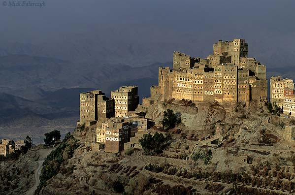 [YEMEN.NORTH 26345] 'Sherege village-1.'  The tower houses of Sherege village catch the golden rays of a late afternoon sun while the Jebel Haras mountains behind it are darkened by a blueish fog. Photo Mick Palarczyk.