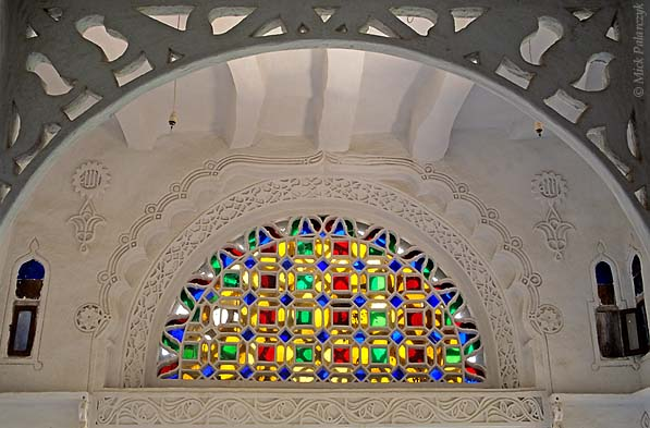 [YEMEN.NORTH 26371] 'Takhrim window.'  A takhrim window in the Rock Palace (Dar al-Hajar) at Wadi Dahr, northwest of Sanaa. These stained-glass windows, which are typical for Yemeni architecture, cast coloured shadows on the walls when the sun is shining through them. Photo Mick Palarczyk.