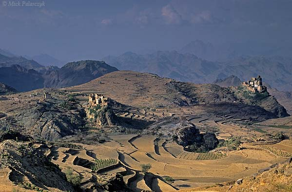 [YEMEN.NORTH 26354] 'Jebel Haras mountains.'  The Jebel Haras mountains south of Manakha are dotted with fortress-like villages, each on its own rocky pedestal and surrounded by terraced fields. To the right: Shargi village. Photo Mick Palarczyk.