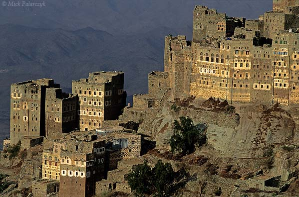 [YEMEN.NORTH 26349] 'Sherege village-2.'  Tower houses of Sherege village in the Jebel Haras mountains. These tower houses have a stable on the ground floor and the manure is shoveled through openings onto the rocky pedestal of the village. Photo Mick Palarczyk.