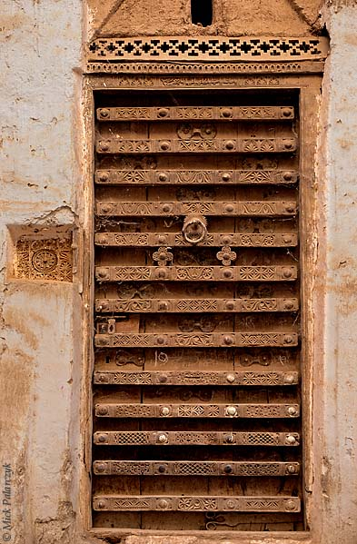 [YEMEN.SOUTH 26581] 'Wooden door in Shibam.'  	A richly decorated wooden door in the northern part of Shibam, an ancient town in the Wadi Hadhramawt. To the left of the door a  circular wooden framed opening, just large enough for the insertion of a person's arm is built into the wall. This allowed the wooden lock to be unlocked from inside with a traditional wooden key. Photo Mick Palarczyk.
