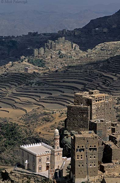 [YEMEN.NORTH 26333] 'Mosque in Ben Ismael.'  In the Jebel Haras mountains south of Manakha the white mosque of Ben Ismael village is dwarfed by neighbouring tower houses. In the background the village of Sherege catches patch of sunlight. Photo Mick Palarczyk.