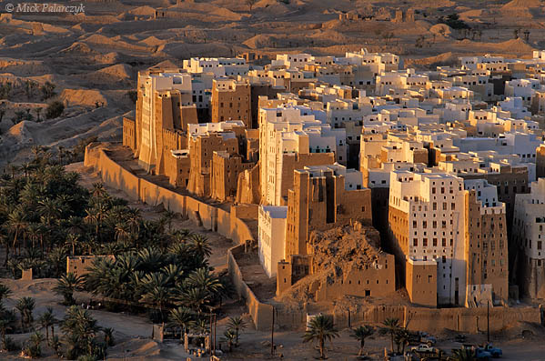 [YEMEN.SOUTH 26547] 'Loam skyscrapers-1.'  	The adobe tower houses of Shibam in the Wadi Hadhramawt are considered the first skyscrapers of the world. Having survived for many centuries, the loam structures are now threatened by modern waterworks, as leaking pipes inside its walls can slowly eat away the loam. Collapse is the inevitable result, as can be seen in the corner house in this picture. Photo Mick Palarczyk.