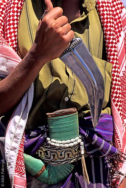 [YEMEN.NORTH 26366] 'Man with jambiya-3.'  Most men in Yemen carry a jambiya, a ceremonial dagger which is a symbol af manly pride. Usually a rosary is strapped around the scabbard of the weapon. Photo Mick Palarczyk.