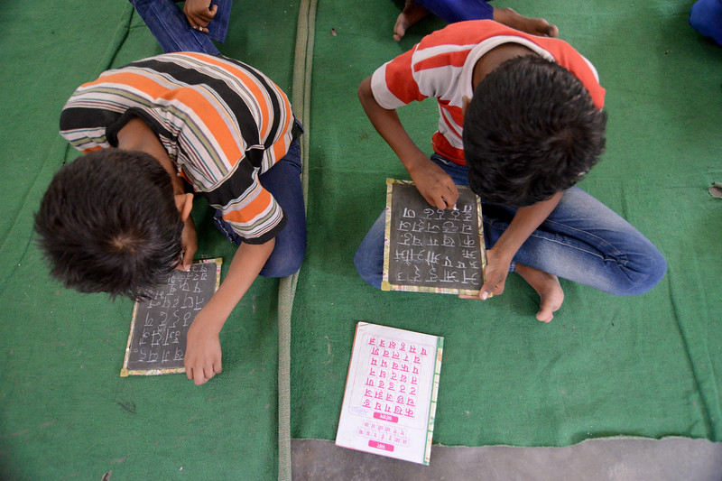 Learning to write the Hindi alphabets. Mukti Ashram is a safe haven for rescued child/bonded labourers till they are repatriated to their parents/guardians. Repatriation may take 6 to 8 weeks till the legal procedures are completed. Children attending Non Formal Education class at Mukti Ashram. A non-Formal education curriculum has been developed for children who had never been in school to teach them simple mathematics and alphabets (Hindi & English).<br /> <br /> Bachpan Bachao Andolan (BBA) is India's pioneering child rights organisation working towards the elimination of all forms of exploitation against children and for free and compulsory education of all children. Over the years BBA has rescued thousands of victims of trafficking, slavery and child labour. Victims are often malnourished, paid meagre wages, if at all, and work extremely long hours in difficult environments.