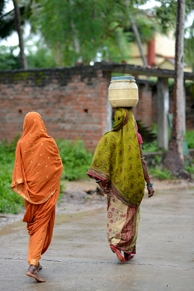 P.Toba in orange saree along with her friend walking in light rain. The lady is carrying water in a can on her head but unlike her from the neighbouring village, women in Jaleripentho village don't have to spend hours filling and carrying water since they receive clean tap water in their homes due to the work of Gram Vikas.<br /> <br /> Gram Vikas' founders came to Orissa in the early 1970s as student volunteers to serve victims of a devastating cyclone. Their extensive activism and relief work motivated them to form Gram Vikas, which was registered on January 22, 1979, and currently serves more than 3,89,333 people in 1196 habitations of 25 districts in Odisha. According to the census data available (2001) Orissa has a population of close to 37 million, of which 88% live in rural areas. Despite its natural advantages, average per capita income is only 73% of the national average, with 47% of the population, around 17.8 million people, living below the poverty line. Poverty is significantly worse in the western and southern districts of the state, which have a higher proportion of adivasis and dalits. Health and education facilities function poorly, communication and transport are underdeveloped.
