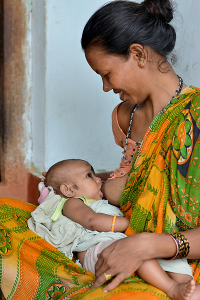 Lalita breast feed her 5 months old baby Susama in Lunduriguda village. Gram Vikas conducts regular community programmes on maternal health, nutrition and cleanliness.<br /> <br /> Literacy rates in rural areas is 58% (71% for males and 44% for females) as compared to the state average of 63% (76% males and 50% females). High rates of infant mortality and maternal mortality contribute to the image of being a poor and backward state. Gram Vikas' founders came to Orissa in the early 1970s as student volunteers to serve victims of a devastating cyclone. They registered in 1979, and currently serves more than 3,89,333 people in 1196 habitations of 25 districts in Odisha.<br /> <br /> Through its direct outreach programmes Gram Vikas works in 943 villages across 23 districts covering 59,132 families of which 39% are adivasis, 14% are dalits and the remainder are from general castes, mostly poor and marginal farmers.