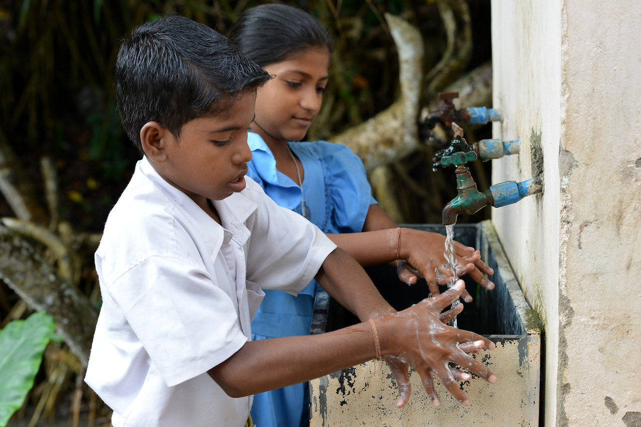 G.Rajesh and P.Sanjana (background) in Jaleripentho village washing their hands with soup under running water after their mid-day meals. Clean tap water for the school by Gram Vikas ensures that the children are healthy and safe.<br /> <br /> Gram Vikas' founders came to Orissa in the early 1970s as student volunteers to serve victims of a devastating cyclone. Their extensive activism and relief work motivated them to form Gram Vikas, which was registered on January 22, 1979, and currently serves more than 3,89,333 people in 1196 habitations of 25 districts in Odisha. Through its direct outreach programmes Gram Vikas works in 943 villages across 23 districts.