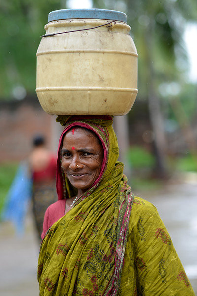 Lady from the neighbouring village of Jaleripentho village walking in light rain carrying water in a can on her head. Women in Jaleripentho village don't have to spend hours filling and carrying water since they receive clean tap water in their homes due to the work of Gram Vikas.<br /> <br /> Gram Vikas' founders came to Orissa in the early 1970s as student volunteers to serve victims of a devastating cyclone. Their extensive activism and relief work motivated them to form Gram Vikas, which was registered on January 22, 1979, and currently serves more than 3,89,333 people in 1196 habitations of 25 districts in Odisha. According to the census data available (2001) Orissa has a population of close to 37 million, of which 88% live in rural areas. Despite its natural advantages, average per capita income is only 73% of the national average, with 47% of the population, around 17.8 million people, living below the poverty line. Poverty is significantly worse in the western and southern districts of the state, which have a higher proportion of adivasis and dalits. Health and education facilities function poorly, communication and transport are underdeveloped.