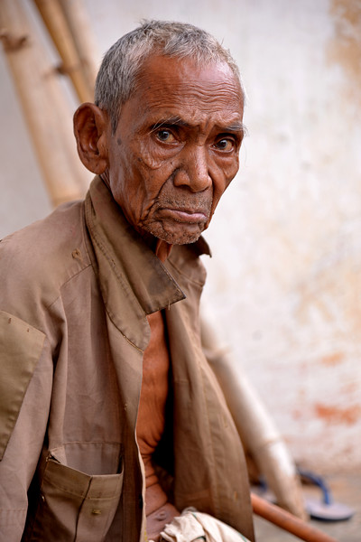 Old man sitting outside his house in the first settlement done by Gram Vikas in Orrisa.<br /> <br /> Gram Vikas' founders came to Orissa in the early 1970s as student volunteers to serve victims of a devastating cyclone. Their extensive activism and relief work motivated them to form Gram Vikas, which was registered on January 22, 1979, and currently serves more than 3,89,333 people in 1196 habitations of 25 districts in Odisha. Through its direct outreach programmes Gram Vikas works in 943 villages across 23 districts covering 59,132 families of which 39% are adivasis, 14% are dalits and the remainder are from general castes, mostly poor and marginal farmers.