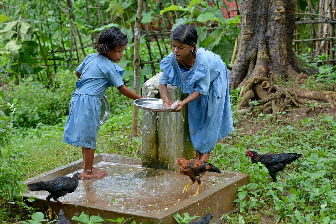 Banita and Bobi washing their plates after having their mid-day meal at school in Lunduriguda village. The running clean water is provided by Gram Vikas.<br /> <br /> Gram Vikas' founders came to Orissa in the early 1970s as student volunteers to serve victims of a devastating cyclone. Their extensive activism and relief work motivated them to form Gram Vikas, which was registered on January 22, 1979, and currently serves more than 3,89,333 people in 1196 habitations of 25 districts in Odisha. <br /> <br /> Through its direct outreach programmes Gram Vikas works in 943 villages across 23 districts covering 59,132 families of which 39% are adivasis, 14% are dalits and the remainder are from general castes, mostly poor and marginal farmers.