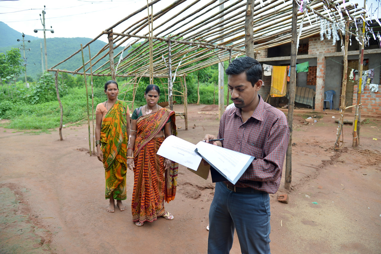 Jyotiprasad from Gram Vikas (foreground) and Bidhulata (middle) with Lalita in Lunduriguda village.<br /> <br /> Literacy rates in rural areas is 58% (71% for males and 44% for females) as compared to the state average of 63% (76% males and 50% females). High rates of infant mortality and maternal mortality contribute to the image of being a poor and backward state. Gram Vikas' founders came to Orissa in the early 1970s as student volunteers to serve victims of a devastating cyclone. They registered in 1979, and currently serves more than 3,89,333 people in 1196 habitations of 25 districts in Odisha.<br /> <br /> Through its direct outreach programmes Gram Vikas works in 943 villages across 23 districts covering 59,132 families of which 39% are adivasis, 14% are dalits and the remainder are from general castes, mostly poor and marginal farmers.