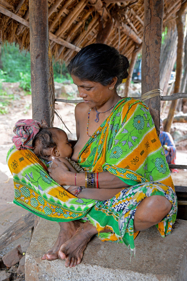 Bhanu Mallik breast feeding her her baby Krusnha  at the cowshed in Lunduriguda village in Orissa.<br /> Gram Vikas provides clean water to the village and also provides training on hygiene and health.<br /> <br /> 80% of the instances of morbidity and mortality cases in rural areas are caused by water-borne diseases. Less than 7% of rural households have access to safe sanitation, less than 20% of rural population has access to protected water and no more than 1% to piped water supply. Through its direct outreach programmes Gram Vikas works in 943 villages across 23 districts covering 59,132 families of which 39% are adivasis, 14% are dalits and the remainder are from general castes, mostly poor and marginal farmers.